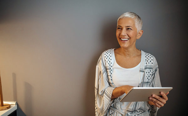 Elderly woman smiling while holding a tablet